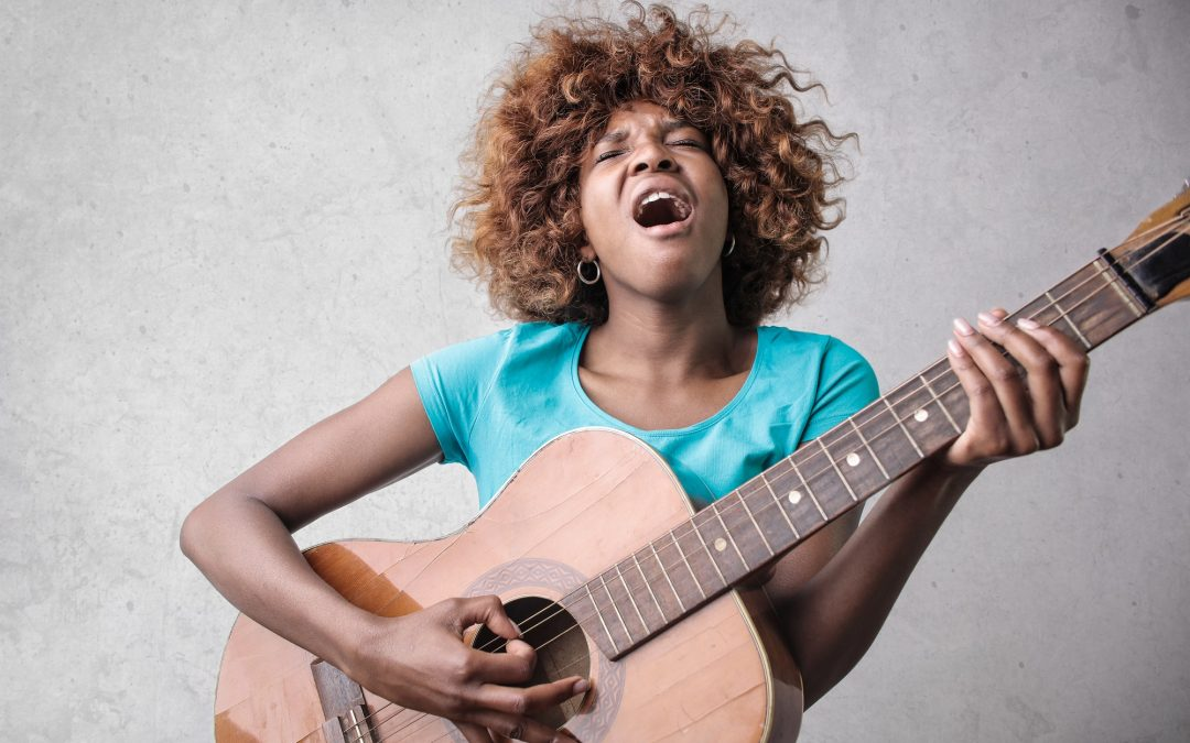 girl playing guitar and singing with her own brand voice